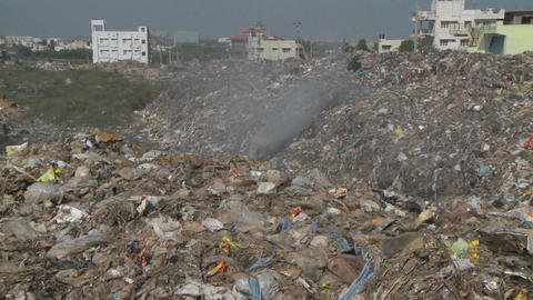 Smoke rises from burning rubbish in a large urban land-fill Stock Video Footage