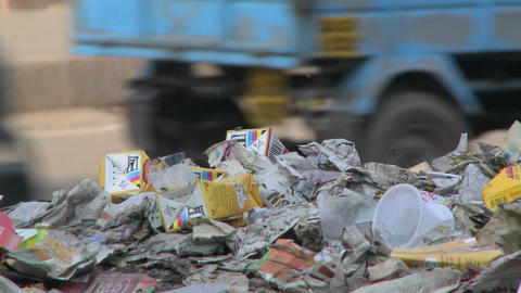 Close view of a pile of trash set on the side of a busy... Stock Video Footage