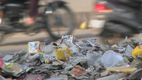 Close view of a pile of trash set on the side of a busy street Footage