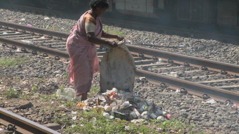 A woman dumps a bag of trash on the railroad tracks Stock Video Footage
