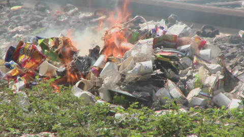Burning rubbish piles close by railroad tracks Stock Video Footage