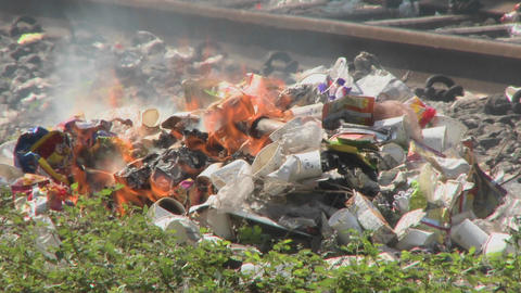 Burning rubbish piles close by railroad tracks Footage