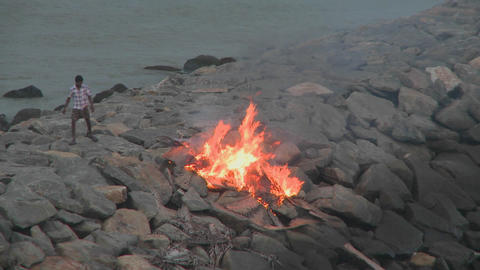 A man throws a piece of rubbish into a burning fire Stock Video Footage