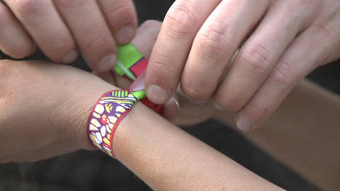 Friendship bracelet being knotted to a wrist Stock Video Footage
