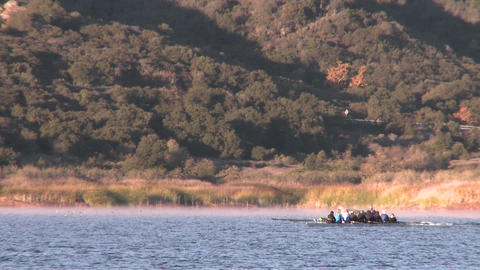 An eight person rowing sweep being followed by their coach on Lake Casitas in Oak View, California Footage