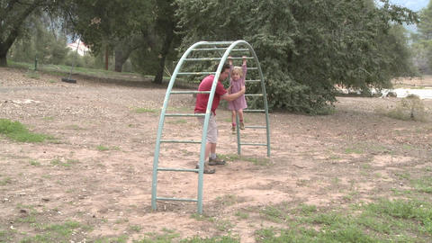 Time lapse of a father and daughter playing on a monkey... Stock Video Footage