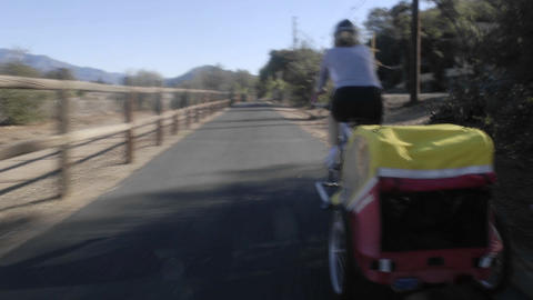 Point of view time lapse of a women riding a bike towing a trailer on the Ojai to Ventura Bike Trail Footage
