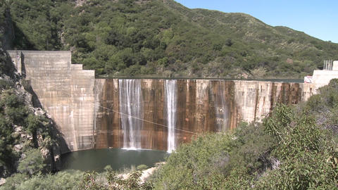 Pan front view of water spilling over the Matilija Dam in Ojai, California Footage