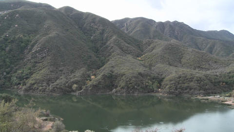Pan of mountains and water in Matilija Reservoir in Ojai, California Footage