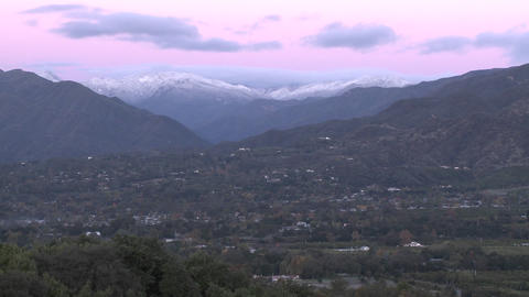 Zoom in of sunrise on the snow-covered Santa Ynez Mountains above Ojai, California Footage
