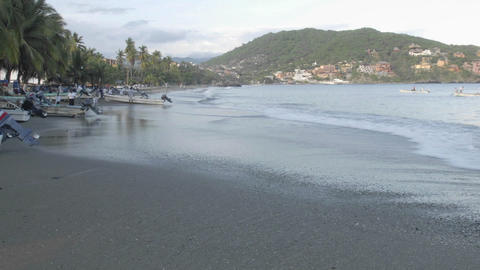 Panning time lapse of fishing boats launching from Playa Principal in Zihuatanejo, Mexico Footage