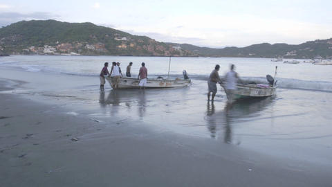 Close up time lapse of fishing boats launching from Playa Principal in Zihuatanejo, Mexico Footage