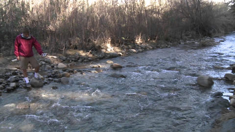 Pan of people testing the water flowing in San Antonio Creek in Ojai, California Footage