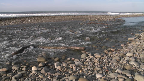Wide pan of water flowing out of the Ventura River estuary into the Pacific Ocean in Ventura, Califo Footage