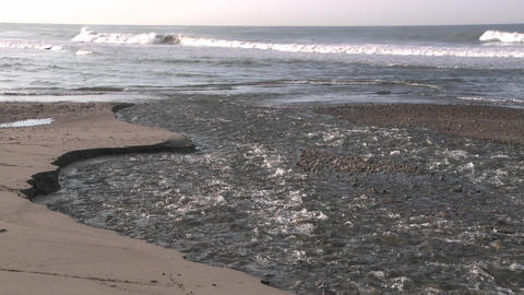 Surfer walking through water flowing out of the Ventura... Stock Video Footage