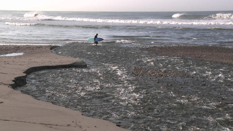 Surfer walking through water flowing out of the Ventura River estuary at Surfers Point in Ventura, C Footage
