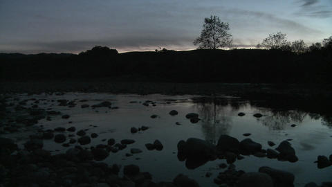 Wide pan at dusk of light reflecting off the Ventura River and the sound of frogs in Oak View, Calif Footage