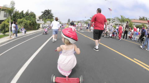 Point of view time lapse of a girl on a tricycle in the Fourth of July Parade in Ventura, California Footage