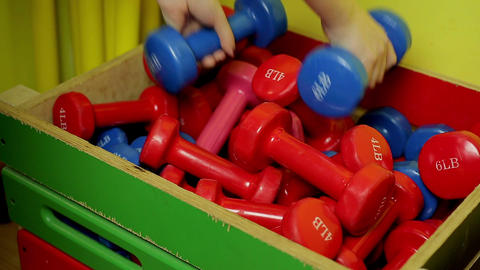 Hands of sportive lady putting dumbbells in the box after active workout in gym Footage