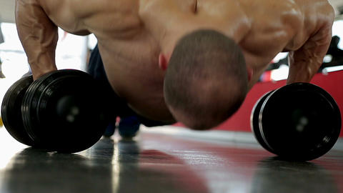 Professional bodybuilder doing dumbbell push-ups, training hard during workout Footage