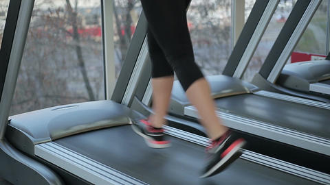 Feet of young sportive woman running fast on treadmill, training for wellness Footage