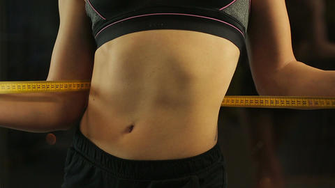 Sexy woman demonstrating her flat belly and fit body, measuring waist with tape Footage
