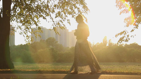 Romantic young woman walking in sun rays, looking for inspiration in the park Live Action