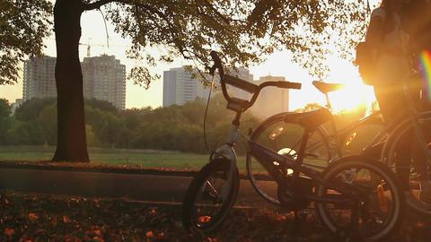 Children's bike left in park standing in sunset rays, happy childhood memories Footage