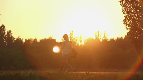 Beautiful young lady walking alone in sunset rays, typing message on smartphone Footage
