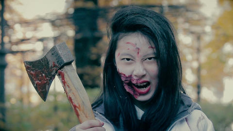 Horrible female killer holding bloody axe in hands, looking fiercely at victim Live Action