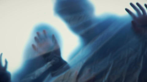 Human silhouettes behind transparent film stretching hands, scary nightmare Live Action