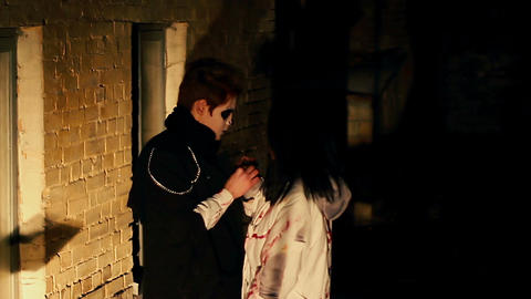 Young couple with scary makeup hugging outside night club, Halloween party Live Action