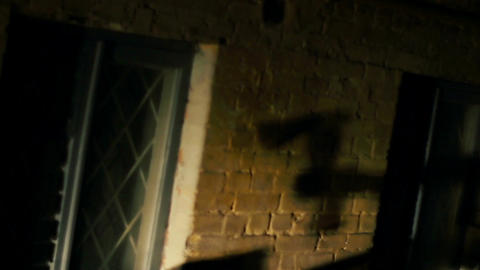 Blood-chilling shadow of killer's hand threatening victim with axe, horror film Live Action