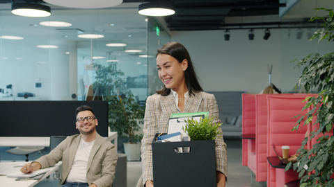 Happy young lady former employee quitting job leaving office room with box of Live Action