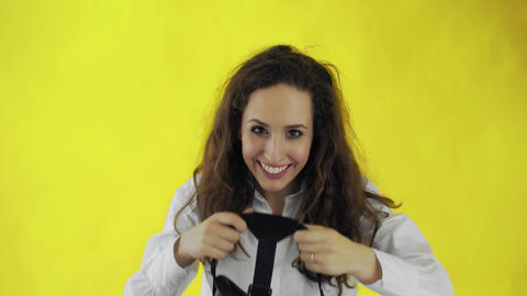 Happy young woman Wearing Virtual Reality Headset on yellow background at studio Live Action