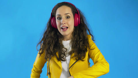 Young woman dancing while listening music on headphones Live Action