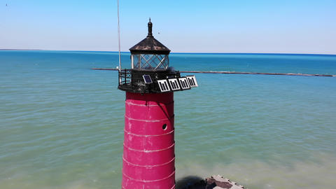 Red lighthouse by the sea on a sunny day. View from a quadcopter on a red Live Action