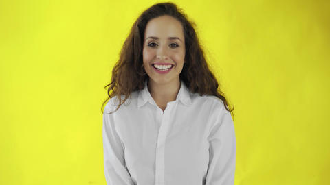 Smiling girl portrait in studio. Cheerful woman smiling face on yellow Live Action
