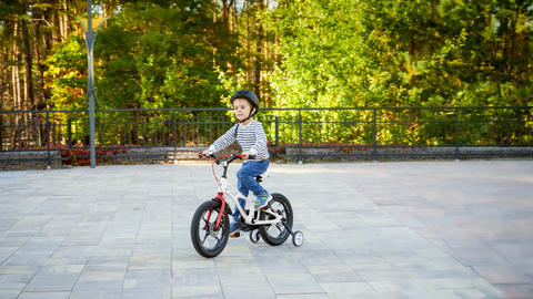 Little 3 years old boy in protective helmet riding his first bicycle at park Photo