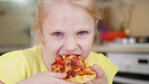 Little girl bites a slice of pizza close up and deliciously eats pizza. The girl Live Action