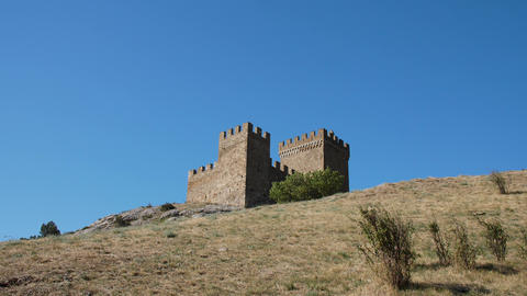 Old massonary of the medeival fortress tower in background of blue skies at top Live Action