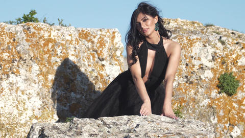 A beautiful woman in a black dress sitting on a rock turning her bare back to GIF