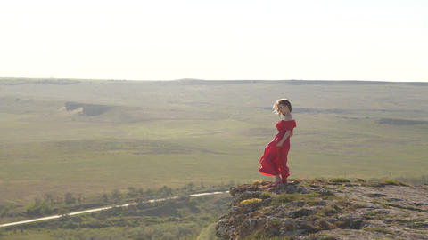 young woman in scarlet fluttering in the wind dresses looking into the distance GIF