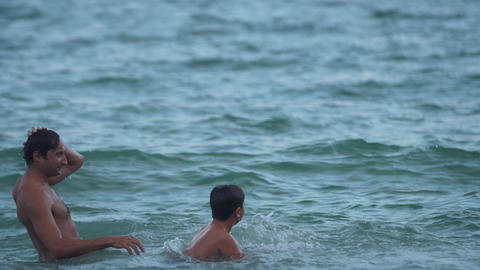 A boy jumps into the water with his father's shoulders Slow motion video GIF