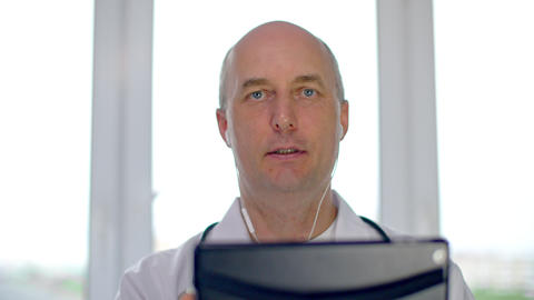 Serious doctor in earphones holding digital tablet and talking during online GIF