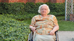 Senior woman in a wheelchair is relaxing in a garden Acción en vivo