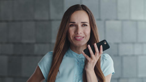 Smiling business woman recording voice message on smartphone in city Live Action