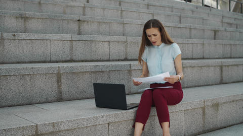 Surprised businesswoman checking information from documents on laptop computer Live Action