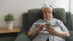 Senior woman is listening music on a smartphone Acción en vivo