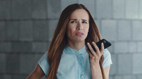 Displeased businesswoman recording voice message on cellphone in city Live Action